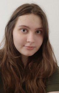 Junge Frau mit halblangen, hellbraunen Haaren in einem olivgrünen Pullover