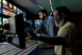 Zwei Männer arbeiten im Schaltraum eines Fernsehsenders.